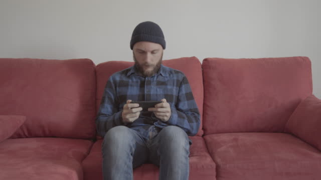 Bearded man at home on a red sofa