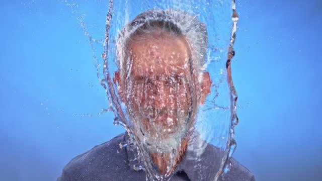 slo-mo-ld-bärtiger mann mit einem spritzer wasser von oben getroffen - splashing stock-videos und b-roll-filmmaterial