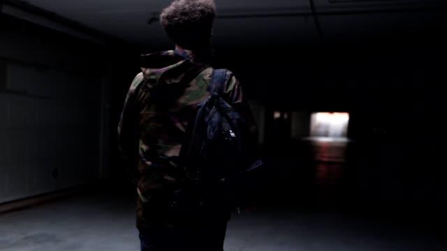 vídeos y material grabado en eventos de stock de hombre barbudo llevando una mochila vestida con chaqueta militar - garaje