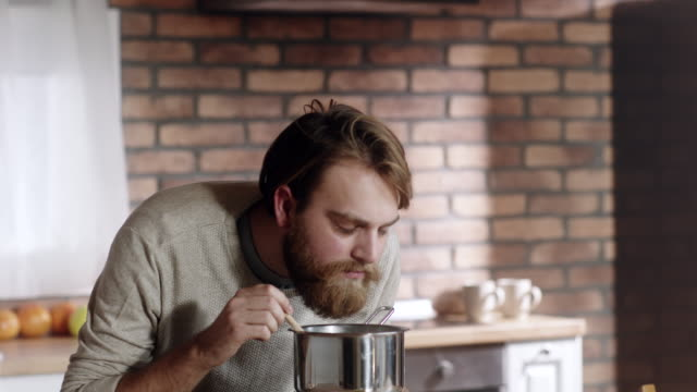 Bearded man cooking in kitchen at home