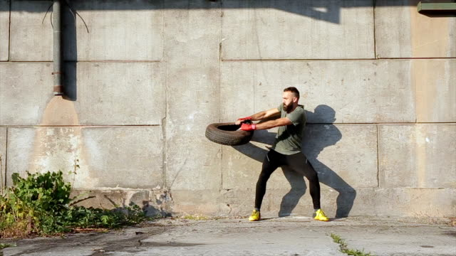 bearded man exercising with a help of a tire - twisted stock videos & royalty-free footage