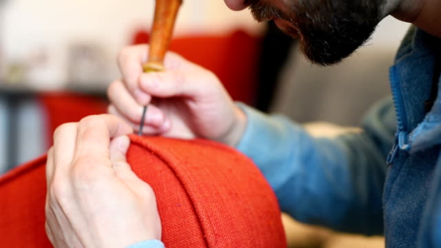 bearded man himself repairs the red chair