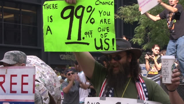 bearded man holds a protest sign and sways to the sound of pounding drums in zuccotti park, during the occupy wall street movement in lower manhattan. - occupy protests stock videos & royalty-free footage