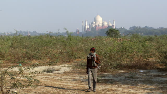 bearded man in hat and scarf walks towards camera, Taj Mahal in background