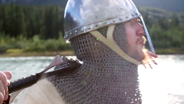 bearded man in medieval/viking costume pauses by river - tied bow stock videos & royalty-free footage