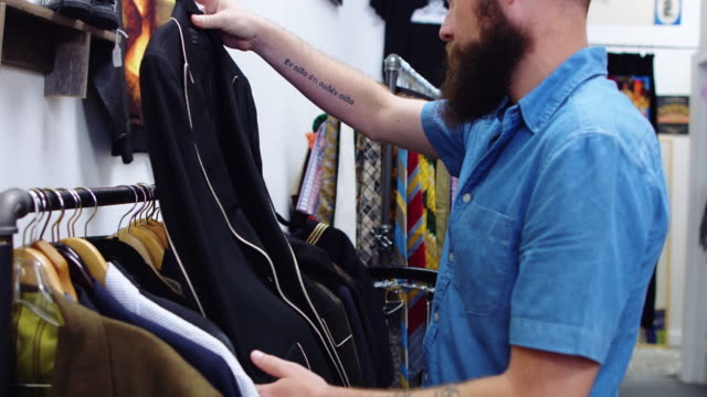 Bearded Man Looking at Second Hand Jackets