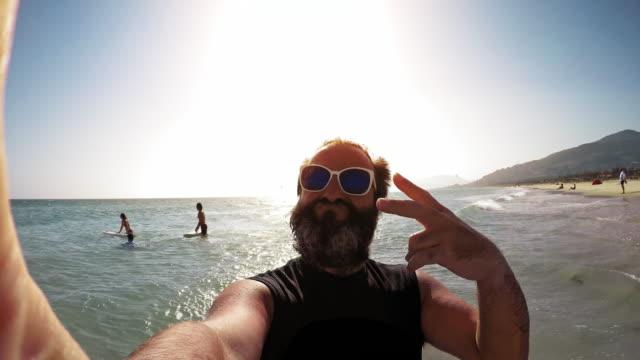 ひげを生やした男スマート フォンを晴れたビーチで彼の友達の作り方 - 中年の男性点の映像素材/bロール