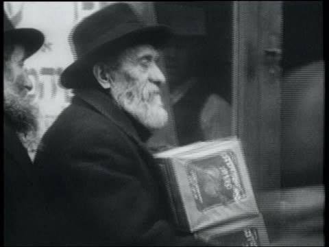 vídeos de stock, filmes e b-roll de b/w 1932 bearded man receiving box of free matzos from shopkeeper / lower east side, nyc - judaísmo
