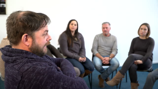4k dolly: bearded man sharing in support group therapy circle - addiction stock videos and b-roll footage