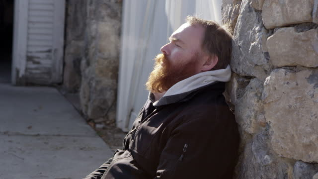 bearded man sitting against a stone wall breathing - stone wall stock videos and b-roll footage