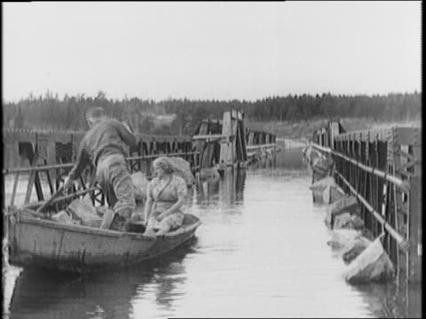 vidéos et rushes de bearded man stands on roof to avoid flooded waters / man and woman steer rowboat down a flooded bridge / stones on bridge to keep it down / two men... - évitement