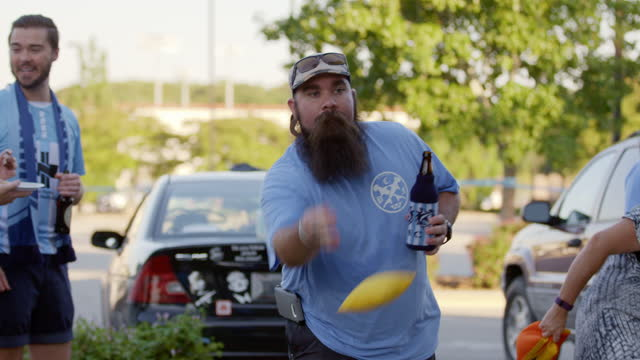 ms. bearded man tosses beanbags in cornhole game while tailgating with friends at local sporting event. - bean bag stock videos & royalty-free footage