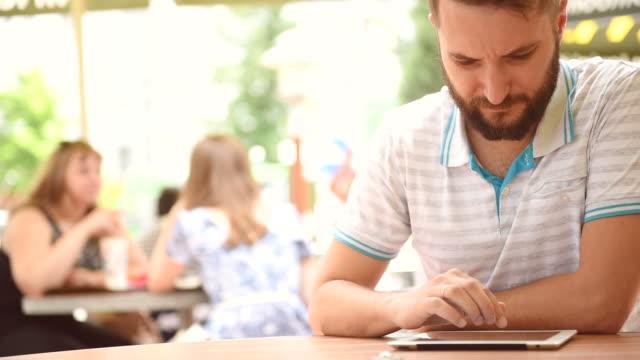 stockvideo's en b-roll-footage met bebaarde man met een tablet in een café close-up - sunny