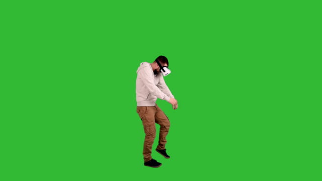 bearded man with glasses of virtual reality frightened and fighting off something on a green background - illusion stock videos and b-roll footage