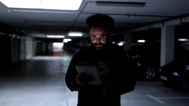 vídeos y material grabado en eventos de stock de hombre barbudo trabajando en una tableta digital mientras está en movimiento - garaje