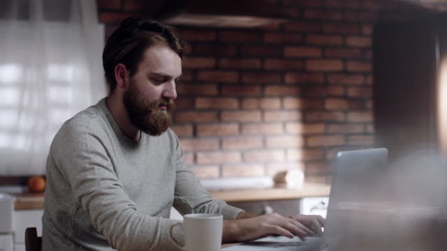 bearded man working on laptop in kitchen at home - beard stock videos and b-roll footage