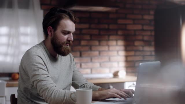 stockvideo's en b-roll-footage met bebaarde man aan het werk op laptop in keuken thuis - baard