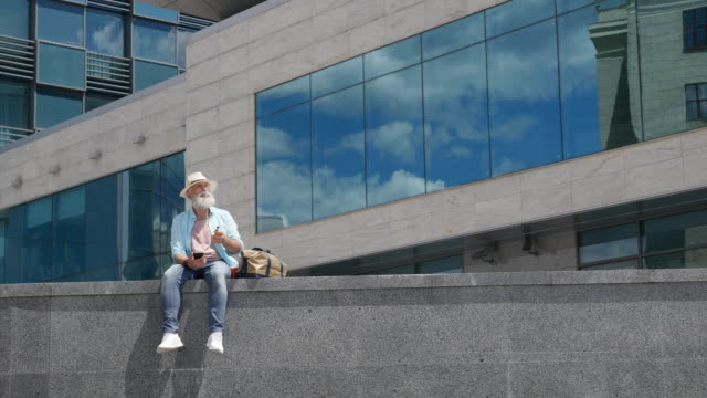 Bearded older man smokes an electronic cigarette in the city