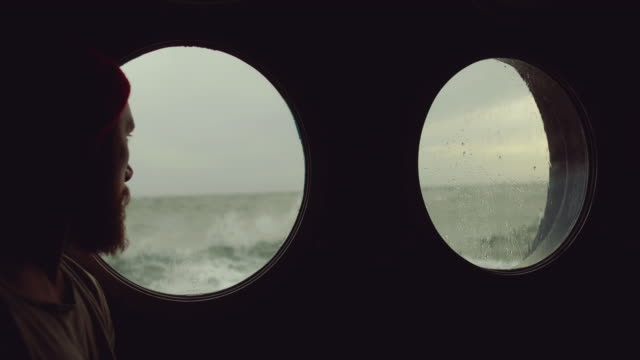bearded sailor at the porthole window of a vessel in a rough sea - avventura video stock e b–roll