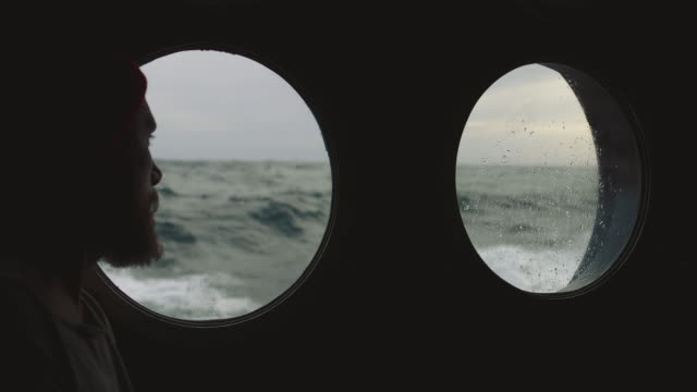 bearded sailor at the porthole window of a vessel in a rough sea - overcast stock videos & royalty-free footage