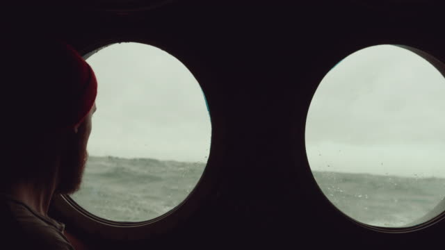bearded sailor at the porthole window of a vessel in a rough sea - marinaio video stock e b–roll