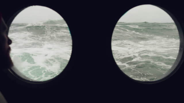 Bearded sailor at the porthole window of a vessel in a rough sea
