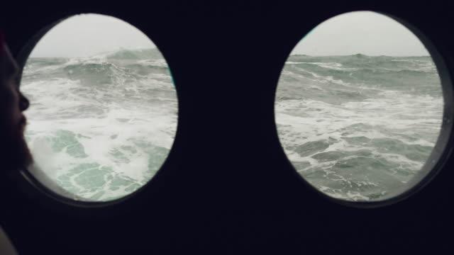 stockvideo's en b-roll-footage met bebaarde matroos op de patrijspoort venster van een vaartuig in een ruwe zee - vissersboot