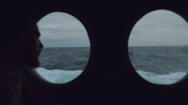 vídeos de stock e filmes b-roll de bearded sailor at the porthole window of a vessel in a rough sea - navio de passageiros