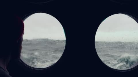 bärtiger seemann am bullauge fenster eines schiffes in rauer see - drehort außerhalb der usa stock-videos und b-roll-filmmaterial