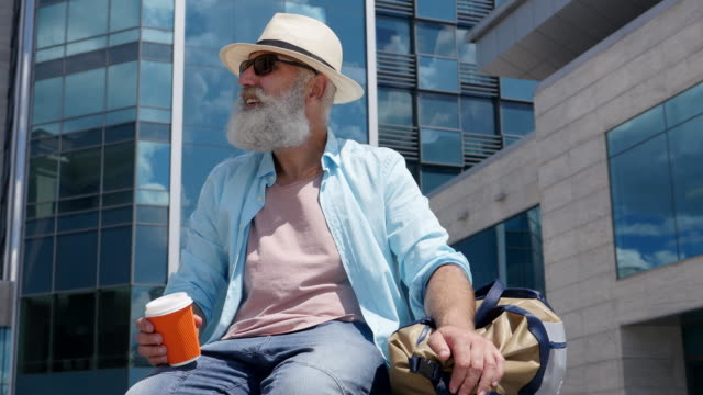 vídeos de stock e filmes b-roll de bearded senior man drinking coffee in the city - cross legged