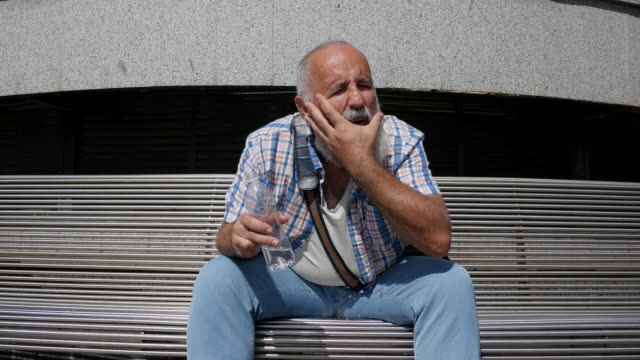 ひげを生やした高齢男は飲料水と彼の頭を douses - ベンチ点の映像素材/bロール