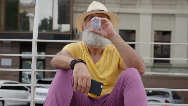 A bearded senior man drinks water in the city