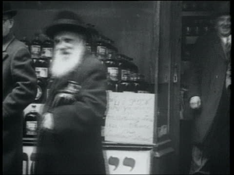 b/w 1932 bearded senior man leaving kosher wine store carrying jug of wine / lower east side, nyc - judaism stock videos & royalty-free footage