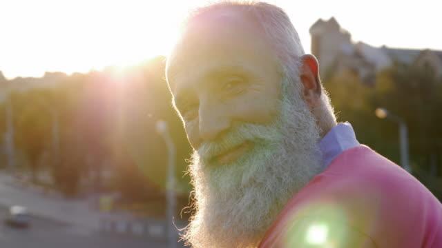 bearded senior man  looks at camera and smiles.