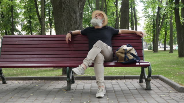 Bearded senior man on a bench in the city