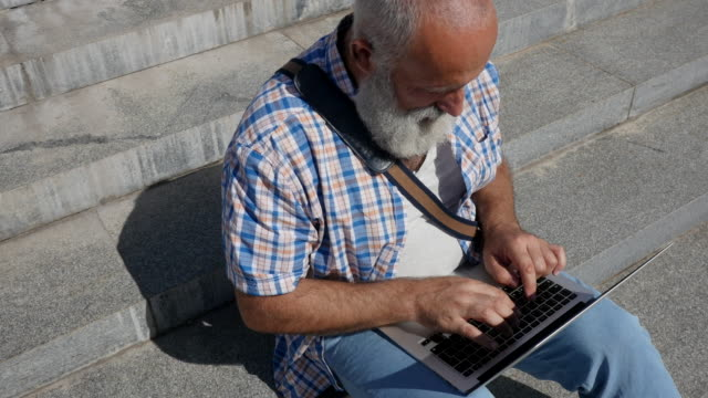 bearded senior man works with a laptop in the city - laptop bag stock videos and b-roll footage