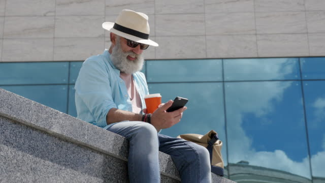 Bearded senior man writes a message on the phone in the city