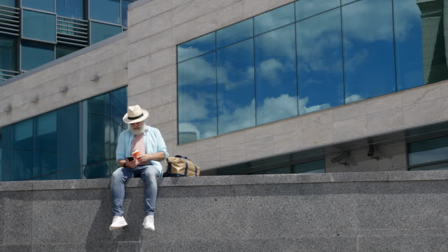 vídeos y material grabado en eventos de stock de hombre mayor con barba escribe un mensaje en el teléfono en la ciudad - cross legged