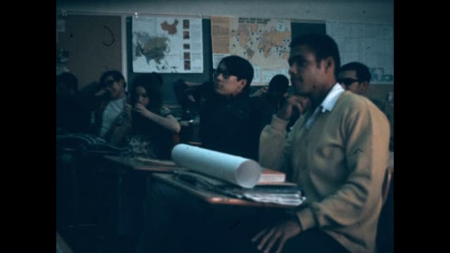 Bearded teacher lecturing his students in a classroom at a community college in Los Angeles from a student film