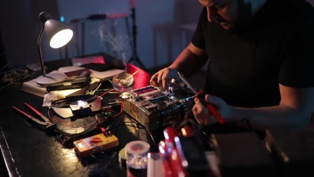 stockvideo's en b-roll-footage met bebaarde terrorist de bouw van een bom in de werkplaats - bomb countdown timer