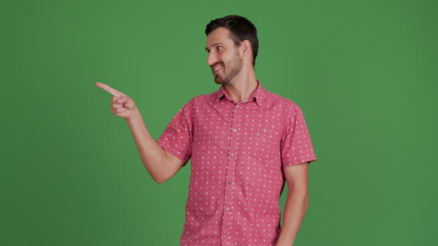 vídeos de stock e filmes b-roll de bearded young adult man showing copy space and showing thumbs up on green background - 30 34 years