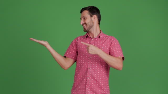 vídeos de stock e filmes b-roll de bearded young adult man showing copy space and showing thumbs up on green background - ficar de pé