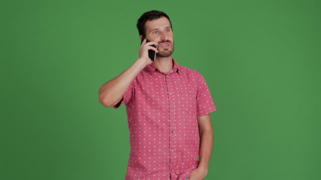 vídeos de stock e filmes b-roll de bearded young adult man speaks on the smartphone on a green background - 30 34 years