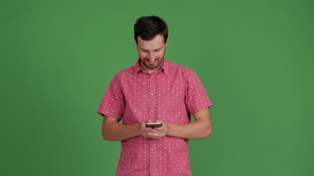 vídeos de stock e filmes b-roll de bearded young adult man uses a smartphone for message on a green background - 30 34 years