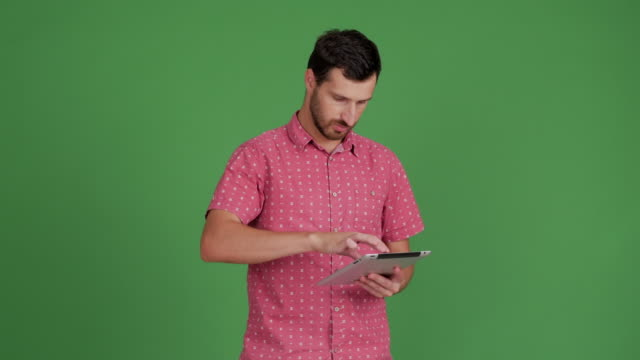 vídeos de stock e filmes b-roll de bearded young adult man uses a tablet for message on a green background - 30 34 years