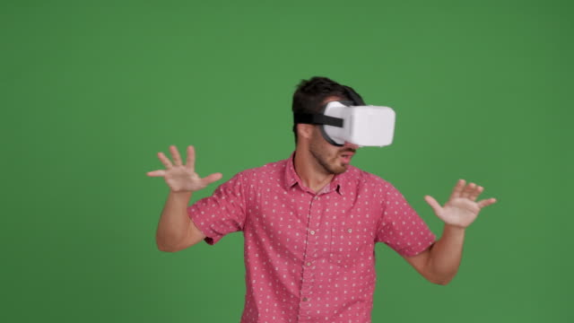 vídeos de stock e filmes b-roll de bearded young adult man with virtual reality glasses on a green background - 30 34 years