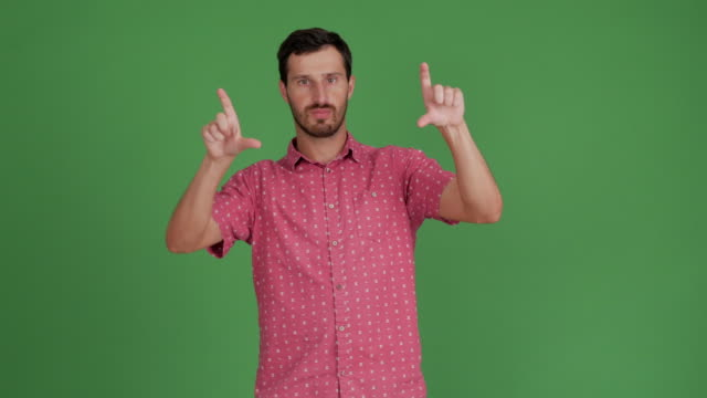 vídeos de stock e filmes b-roll de bearded young man uses his hands virtual space on a green background - 30 34 years