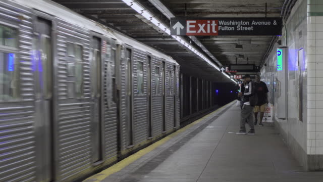 beat up, old c train stops at platform in brooklyn subway station. - metropolitana di new york video stock e b–roll