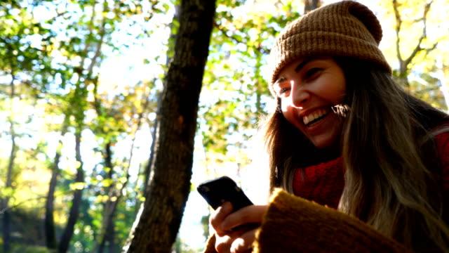 美しい女の子笑色補正なしのスマート フォンを使用して - 若い女性だけ点の映像素材/bロール