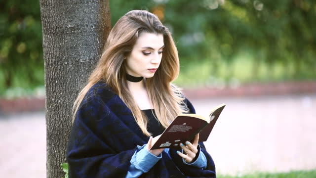 vídeos y material grabado en eventos de stock de libro de lectura de la hermosa muchacha en el parque - sólo una adolescente